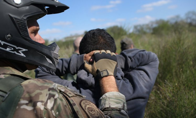 A US border patrol agent leads undocumented immigrants through the brush after capturing them near the Mexico border near Rio Grande City, Texas. Photograph: John Moore/Getty Images